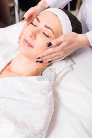 Photo pour Esthéticienne donnant massage manuel du visage à la femme allongée sur peignoir et bandeau au salon de beauté - image libre de droit