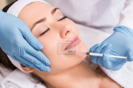 Photo pour Cosmétologue faire une injection sur le visage à la femme au salon de beauté - image libre de droit