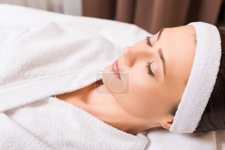 Photo for Woman lying in white bathrobe and closed eyes at beauty salon - Royalty Free Image