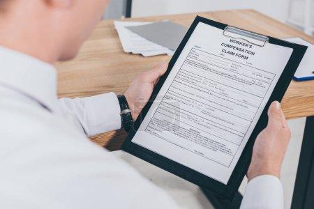 Photo pour Vue recadrée d'homme d'affaires adulte lire le formulaire de demande d'indemnisation au lieu de travail - image libre de droit