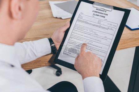 Photo pour Vue recadrée d'homme d'affaires lire le formulaire de demande d'indemnisation - image libre de droit