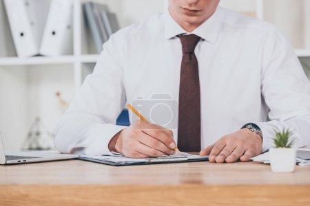 Photo pour Vue recadrée d'homme d'affaires de remplissage dans la demande d'indemnisation à l'espace de travail - image libre de droit