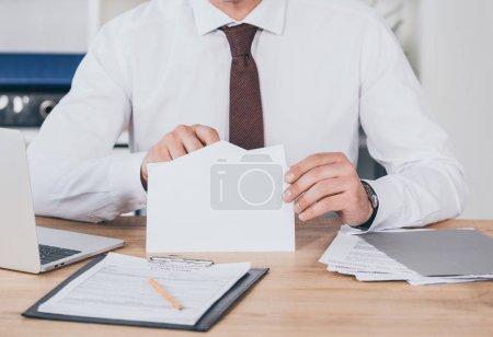 vue recadrée de l'homme d'affaires ouverture enveloppe dans le bureau, concept de rémunération