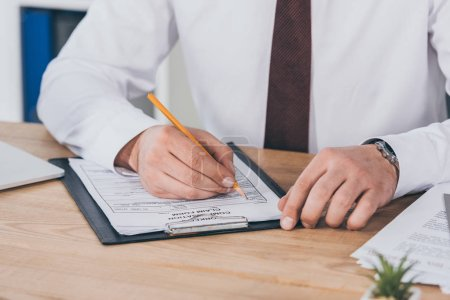 Photo for Cropped view of businessman writing on compensation claim form at workplace - Royalty Free Image
