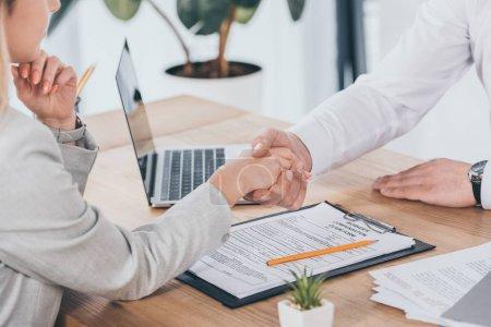 Photo pour Recadrée vue des mains tremblante d'affaires avec femme au lieu de travail, notion de compensation - image libre de droit