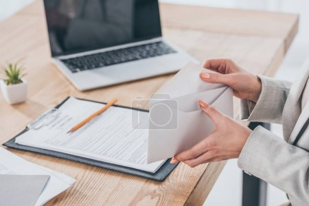 Photo for Partial view of businesswoman holding open envelope in hands at workspace, compensation concept - Royalty Free Image