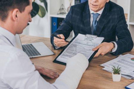 Photo pour Homme d'affaires en veste bleue donnant forme à une demande d'indemnisation au travailleur avec bras cassé à la table au bureau, concept d'indemnisation - image libre de droit