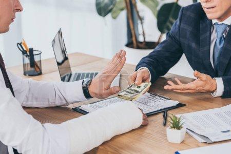 Photo pour Vue recadrée du travailleur rejetant l'argent donnant homme d'affaires en veste bleue au bureau, concept de compensation - image libre de droit