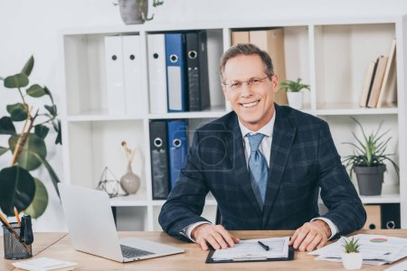 Photo pour Homme d'affaires en veste bleue, assis à table avec des documents et le sourire au bureau, le concept de compensation - image libre de droit