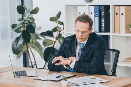Photo for Businessman in blue jacket sitting at table with documents and looking on watch in office, compensation concept - Royalty Free Image