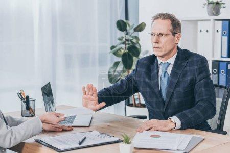 Photo pour Homme d'affaires assis à table et rejetant l'enveloppe ce qui donne de la femme dans le bureau, la notion de compensation - image libre de droit