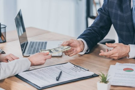 Photo for Cropped view of businessman sitting at table and taking money from woman in office, compensation concept - Royalty Free Image