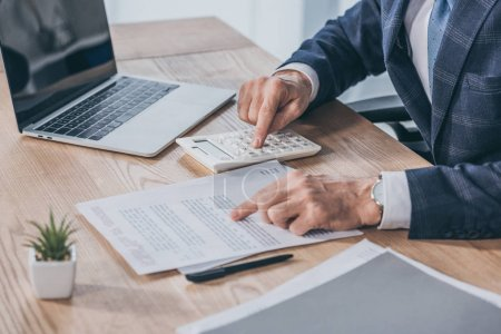 Photo for Cropped view of businessman sitting at table, reading document and counting with calculator in office, compensation concept - Royalty Free Image