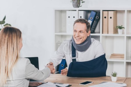 Foto de Mujer rubia estrecharme la mano con trabajador en vendaje de apoyo y el brazo de cuello sobre la mesa en la oficina, en concepto de compensación - Imagen libre de derechos