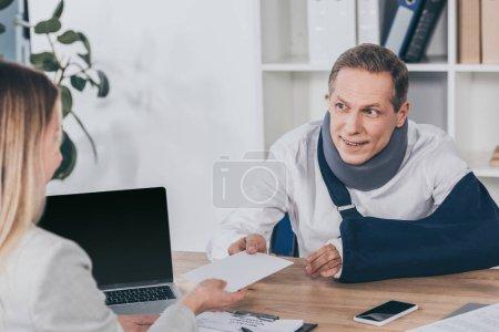 Foto de Trabajador en vendaje con soporte y brazo de cuello sentado en la mesa y dando sobres para mujer en oficina, concepto de compensación - Imagen libre de derechos
