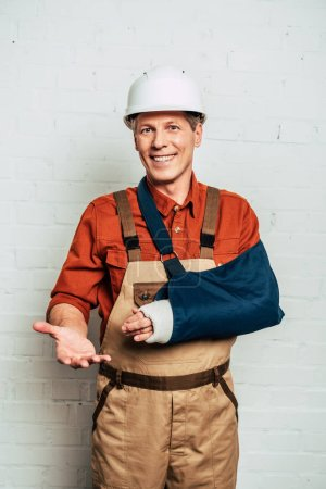 Foto de Reparador con vendaje de brazo sobre fondo con textura blanco - Imagen libre de derechos