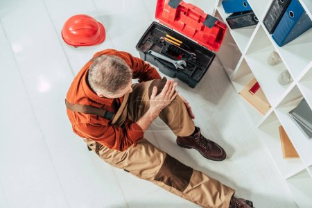 Photo for Top view of repairman sitting on floor and holding injured knee surrounding by equipment in office - Royalty Free Image