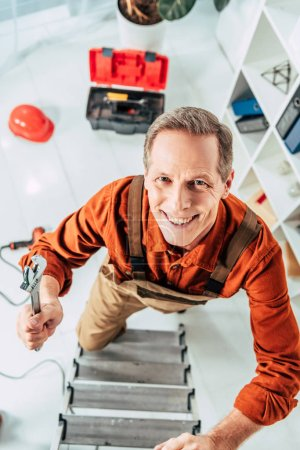 Photo for Top view of climbing repairman on ladder with wrench and smiling in office - Royalty Free Image
