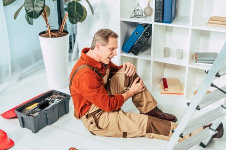 Photo for Repairman sitting on floor and holding injured knee surrounding by equipment in office - Royalty Free Image