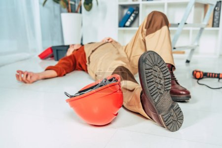 Photo for Repairman lying on white floor in uniform in office - Royalty Free Image