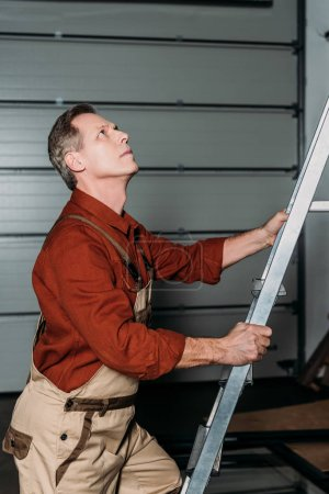 Photo for Repairman in orange uniform climbing on ladder in garage - Royalty Free Image