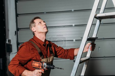 Photo for Repairman climbing with screwdriver on ladder in garage - Royalty Free Image