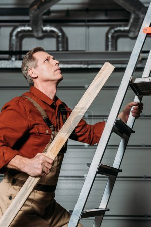 Photo for Repairman in orange uniform climbing with wooden board in hand on ladder in garage - Royalty Free Image
