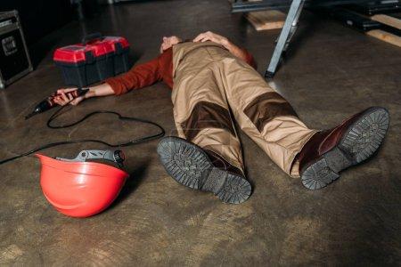 Photo pour Réparateur couché sur le sol en uniforme près de l'échelle et tenant tournevis dans le garage - image libre de droit
