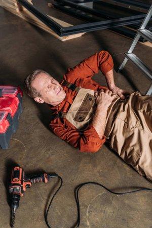 Photo pour Réparateur âgé moyen, allongé sur le sol près d'échelle et la tenue de côté dans le garage - image libre de droit