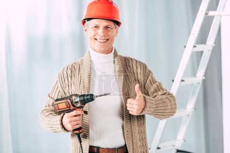 Photo for Middle aged man in beige cardigan holding screwdriver at home - Royalty Free Image