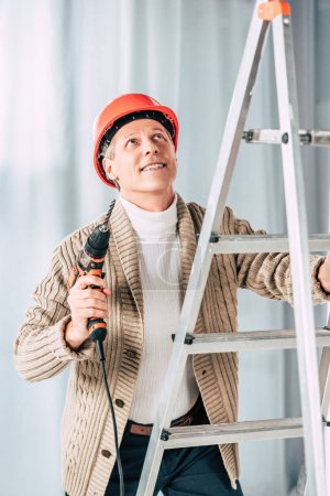 Photo for Middle aged man in beige cardigan climbing with screwdriver on ladder at home - Royalty Free Image