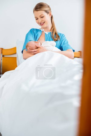 Photo for Selective focus of beautiful happy young mother breastfeeding newborn baby on bed in hospital room - Royalty Free Image