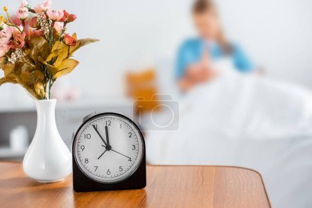 Photo for Clock, flowers in vase and mother with newborn baby behind in hospital room - Royalty Free Image