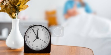 Photo for Close-up view of clock, flowers in vase and mother with newborn baby behind in hospital room - Royalty Free Image