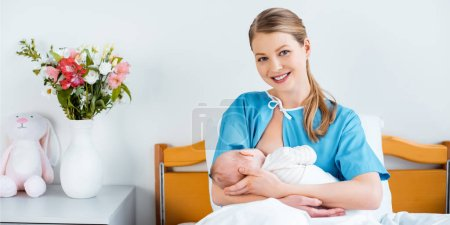 Photo for Happy young mother sitting in bed and smiling at camera while breastfeeding newborn baby in hospital room - Royalty Free Image