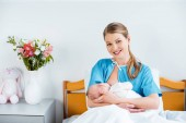 happy young mother sitting in bed and smiling at camera while breastfeeding newborn baby