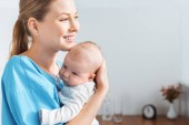 side view of happy young mother holding adorable baby and looking away in hospital room