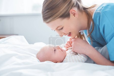 Photo for Side view of happy young mother holding hands of adorable baby in hospital room - Royalty Free Image