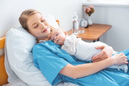 Photo for Young mother sleeping on hospital bed with adorable baby lying on chest - Royalty Free Image