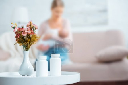 Photo for Containers with pills, flowers in vase and mother breastfeeding baby behind at home - Royalty Free Image