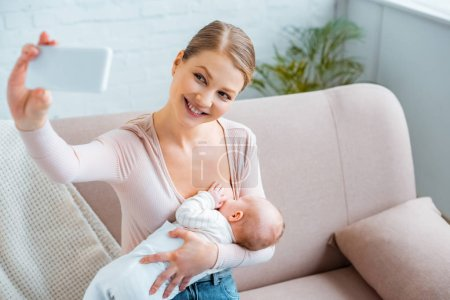 Photo for Happy young woman breastfeeding baby and taking selfie with smartphone at home - Royalty Free Image
