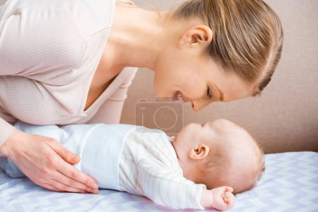 Photo for Side view of happy young mother looking at adorable child lying on couch - Royalty Free Image