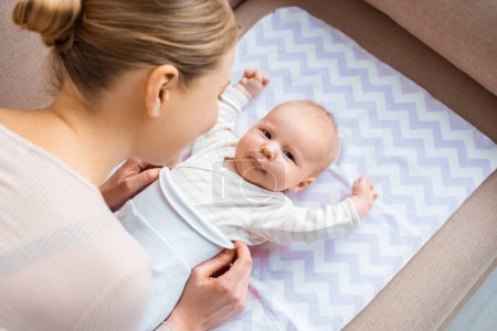 Photo for High angle view of mother putting clothes on adorable infant baby - Royalty Free Image