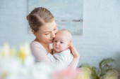 selective focus of happy young mother hugging adorable baby at home