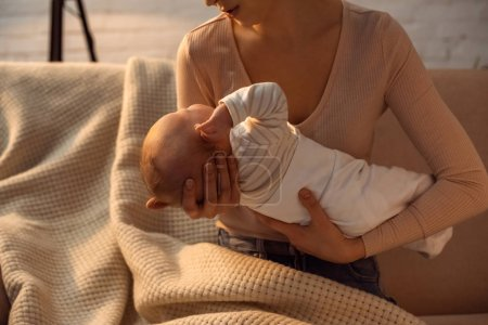 Photo for Cropped shot of young mother holding baby during breastfeeding at night - Royalty Free Image