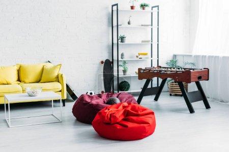Foto de Amueblado amplio salón con sillas PUF, sofá y fútbol de mesa - Imagen libre de derechos