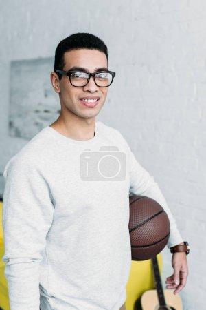 Photo pour Jeune homme métis en sweat-shirt blanc et lunettes tenant le ballon et regardant la caméra - image libre de droit