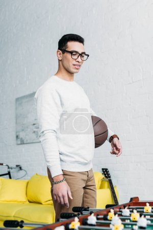 young mixed race man in white sweatshirt standing by football table