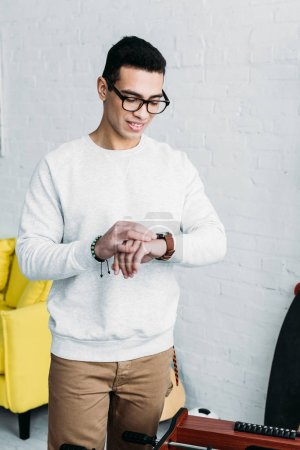 Photo for Handsome mixed race man in white sweatshirt checking time on wristwatch - Royalty Free Image