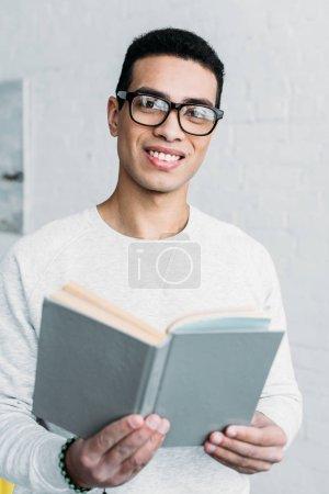 sonriente mestizo joven en gafas sosteniendo libro y mirando a la cámara